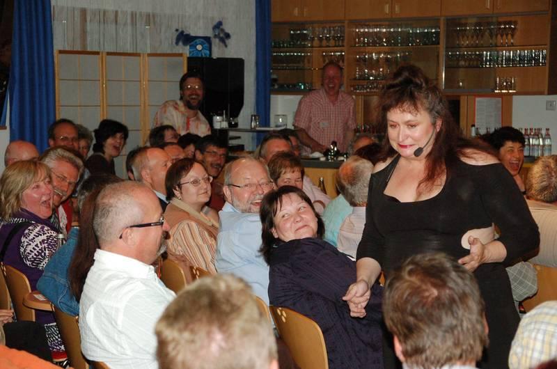 Nach der Pause schwarz, enganliegend, durchschimmernd – und mit originellem Rückendekollete: Lizzy Aumeier beeindruckte in der ARCHE auch optisch. Hier sucht sie nach Männern im Publikum – und findet